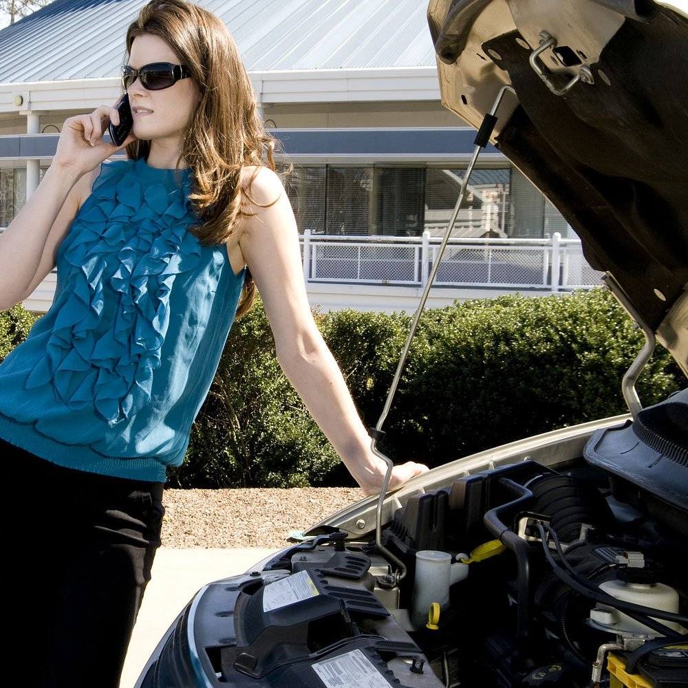 A pretty woman dressed in business attire stranded on the side of the road and calling for roadside assistance