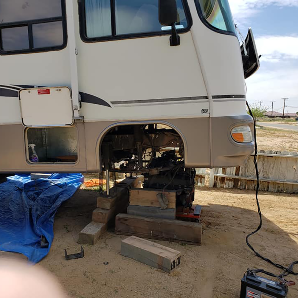 An RV up on blocks in a backyard being repaired by MechaMedix traveling RV